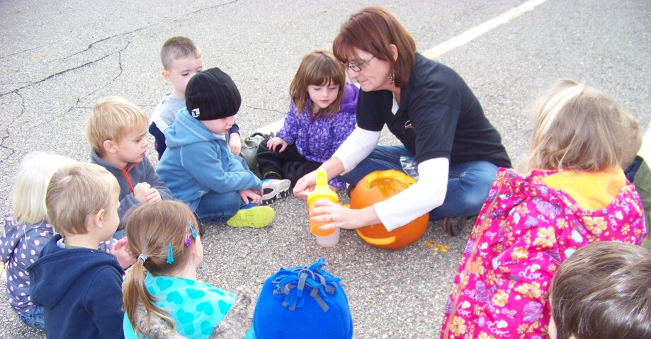 Picture of a teacher and students carving a pumpkin